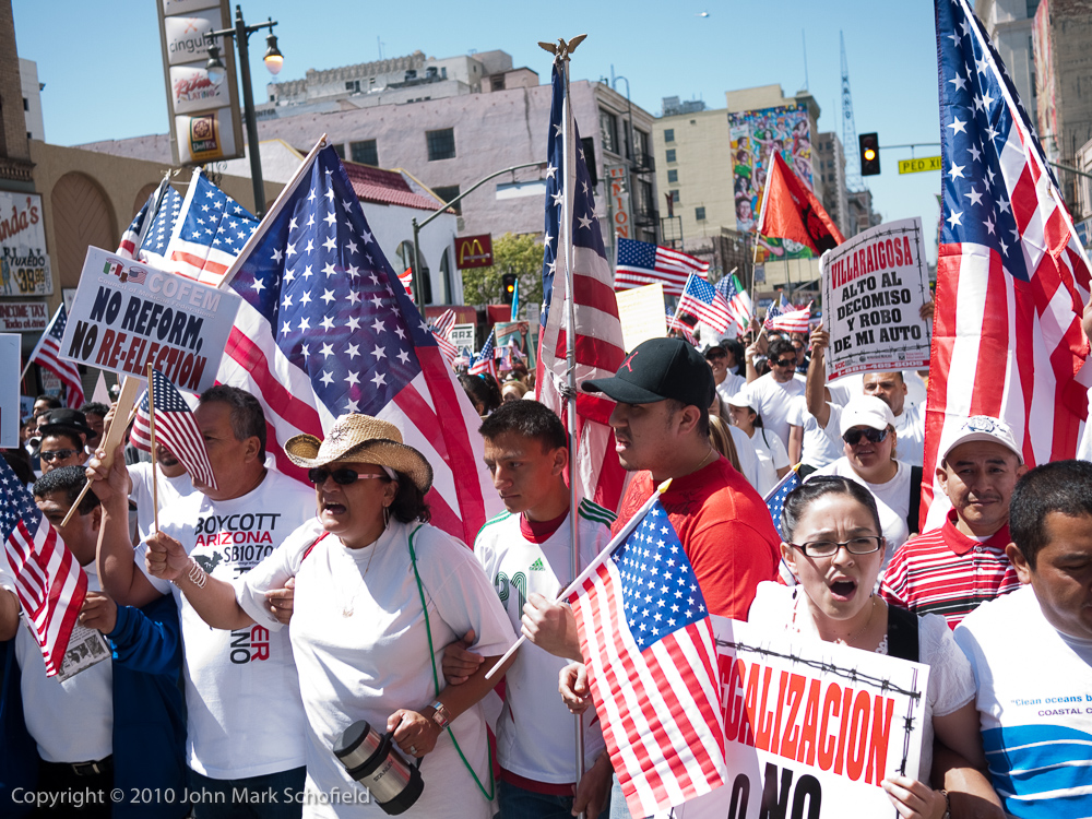 Immigration reform protestors wearing white shirts and carrying lots of flags